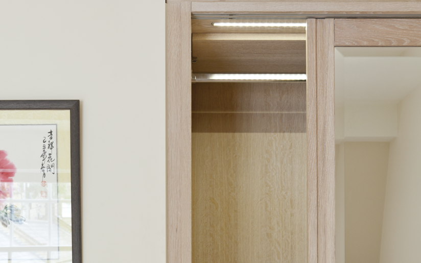 Wardrobe Partial Interior...view where the open solid oak framed mirrored sliding door, chromed hanging rail and lighting can be seen.